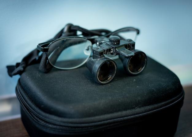 Óculos médicos odontológicos com lentes binoculares, em clínica odontológica. óptica dentária. equipamentos de tecnologia moderna Foto Premium