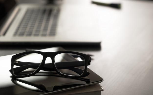 Óculos na mesa de escritório com computador notebook Foto Premium
