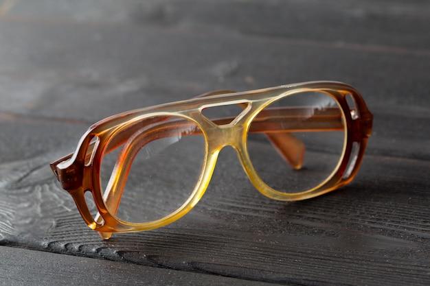 Óculos na mesa de madeira Foto Premium