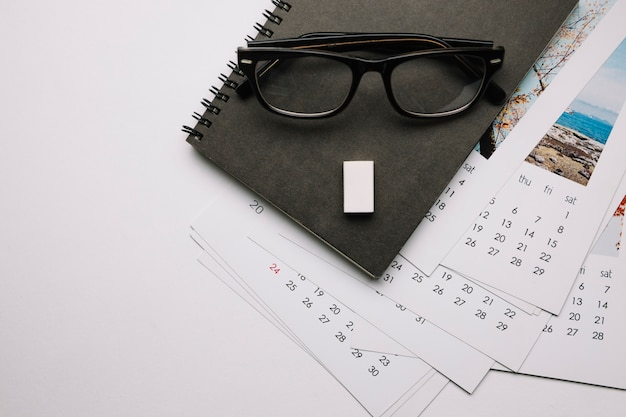 Óculos no caderno e calendários Foto gratuita