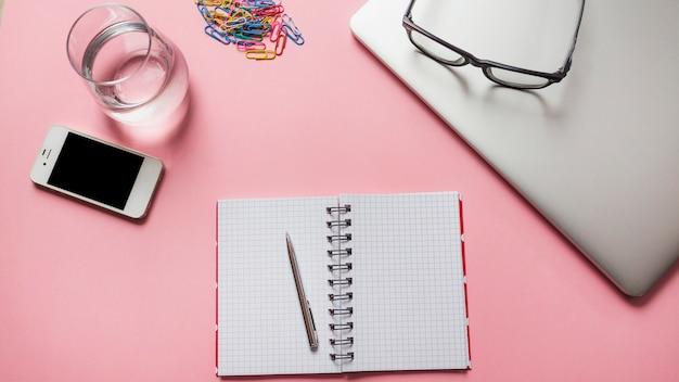 Óculos no laptop com artigos de papelaria; smartphone e copo de água no fundo rosa Foto gratuita