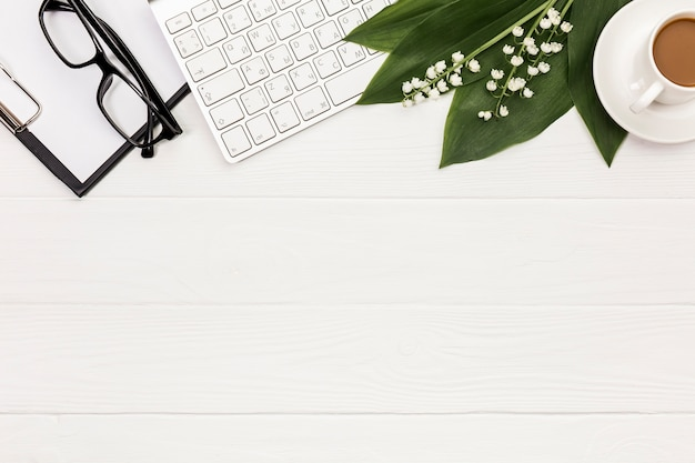 Óculos, prancheta, teclado, flor e folhas com xícara de café na mesa de escritório Foto gratuita
