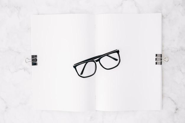Óculos preto sobre o papel branco anexar com dois clipes de bulldog no pano de fundo de mármore Foto gratuita