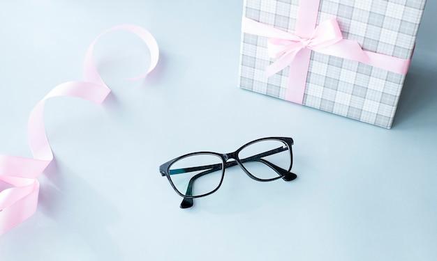 Óculos pretos e caixa de presente em fundo azul claro Foto Premium