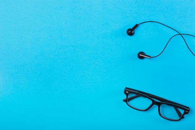 Óculos pretos e fone de ouvido no fundo azul Foto gratuita