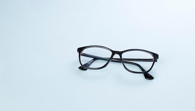 Óculos pretos em imagem de fundo azul claro com espaço de cópia Foto Premium
