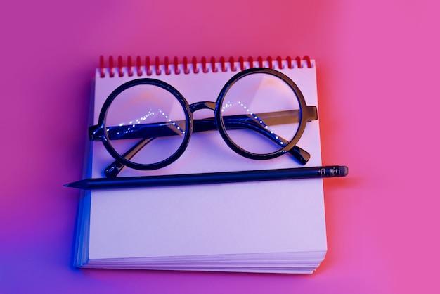Óculos redondos pretos mentem em um bloco de notas na luz de neon em fundo rosa Foto Premium