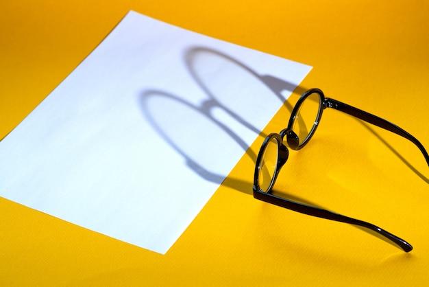 Óculos redondos pretos sobre um fundo amarelo com sombra dura e o visual da inscrição Foto Premium