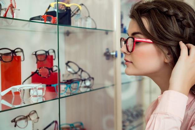 Óculos sempre não são suficientes. retrato lateral da mulher moderna bonita em óculos transparentes, olhando para o carrinho com óculos e escolhendo entre uma variedade de quadros, querendo comprar algo novo Foto gratuita