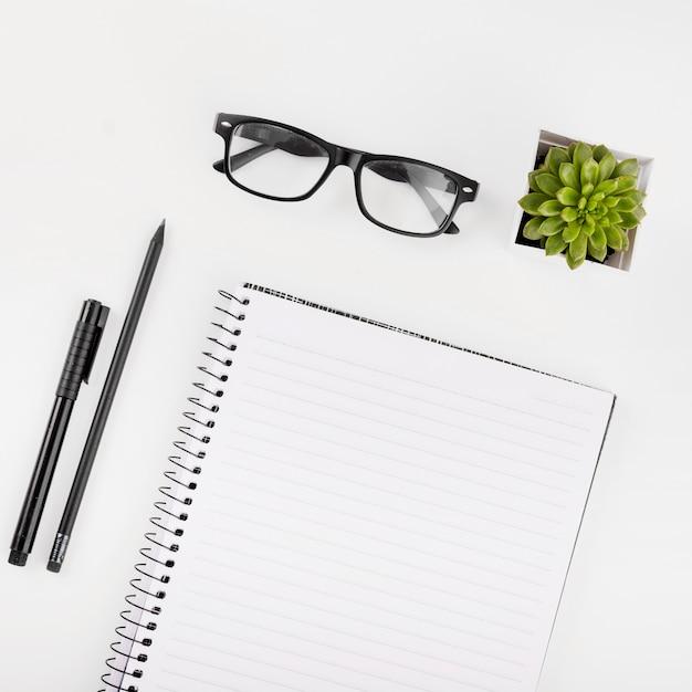 Óculos; vaso de planta; bloco de anotações; caneta e lápis sobre fundo branco Foto gratuita