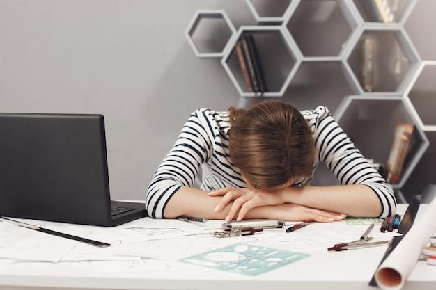 Ocupação profissional e excesso de trabalho. feche de cansada jovem bonita engenheiro garota com cabelo escuro em roupas listradas, deitado nas mãos no escritório, sofrendo de dor de cabeça após um longo dia de trabalho. Foto gratuita