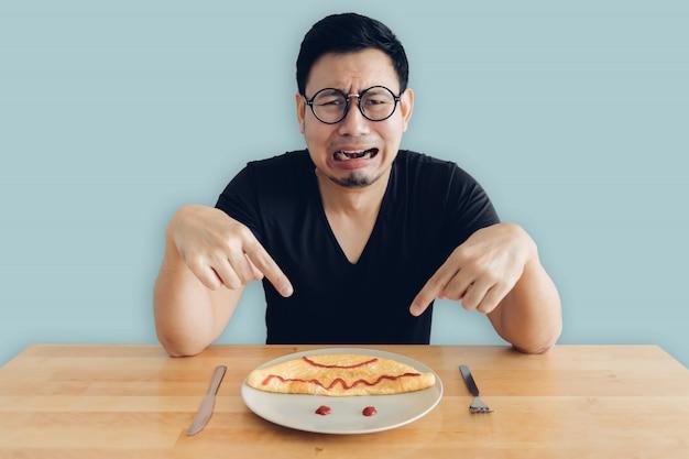 Odeio e choro homem asiático está comendo café da manhã caseiro conjunto de omelete. Foto Premium