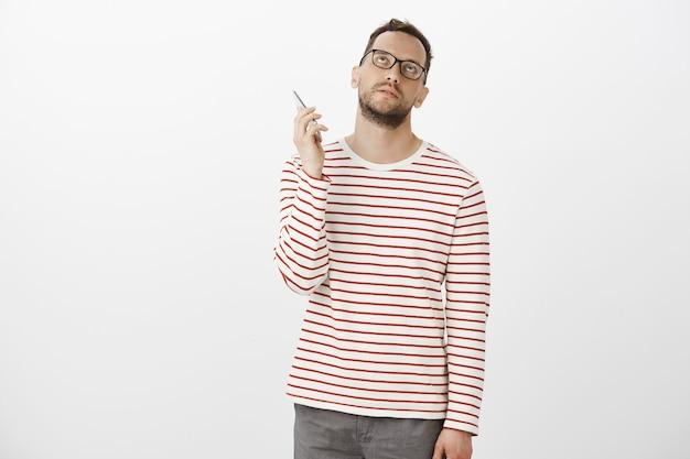 Odeio pendurar no telefone. homem europeu atraente de óculos incomodado e irritado Foto gratuita