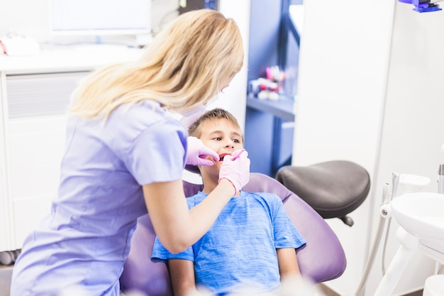 Odontólogo, fazendo, tratamento dental, de, um, menino, em, clínica Foto gratuita