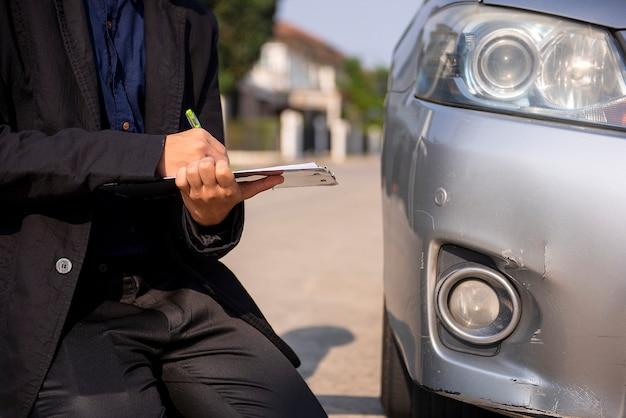 Oficiais da companhia de seguros verificam os estragos do carro dos acidentes de trânsito Foto Premium