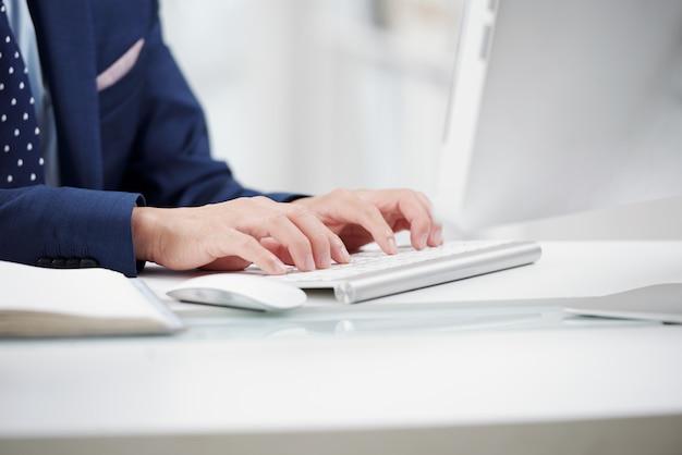 Oficial anônimo recortado digitando no teclado branco Foto gratuita