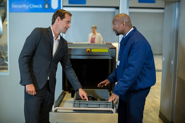 Oficial de segurança do aeroporto interagindo com o passageiro ao verificar um pacote Foto gratuita
