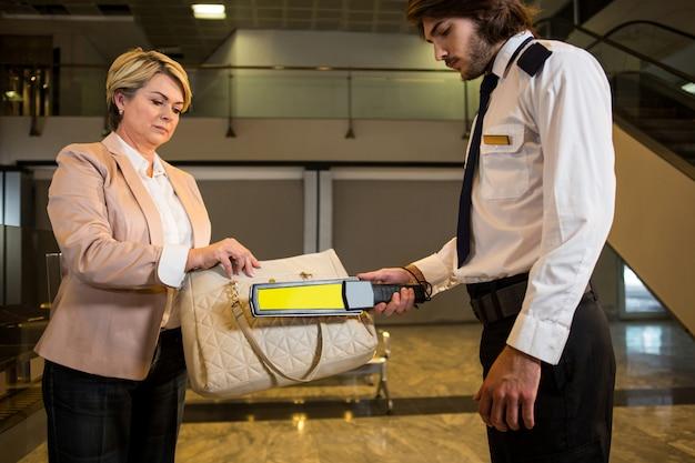 Oficial de segurança do aeroporto usando um detector de metais para verificar uma mala Foto gratuita