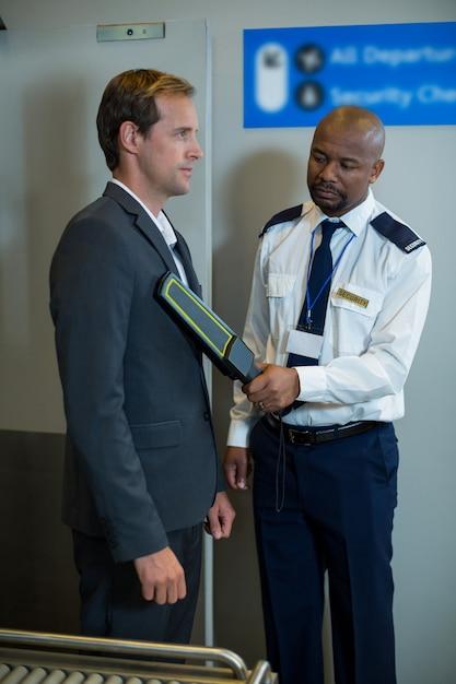 Oficial de segurança do aeroporto usando um detector de metais portátil para verificar um passageiro Foto gratuita