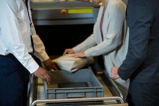 Oficial de segurança do aeroporto verificando a mala do passageiro Foto gratuita