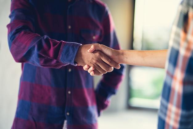 Oficial está feliz e aperta a mão para celebrar em sucesso do fim em um plano de trabalho Foto Premium