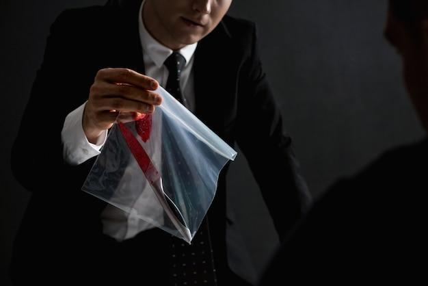 Oficial mostrando uma evidência em investigação criminal Foto Premium