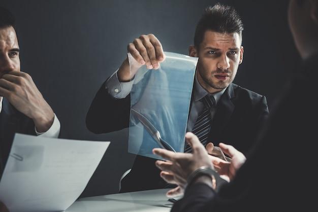 Oficial na sala de interrogatório mostrando uma faca como prova de assassinato Foto Premium