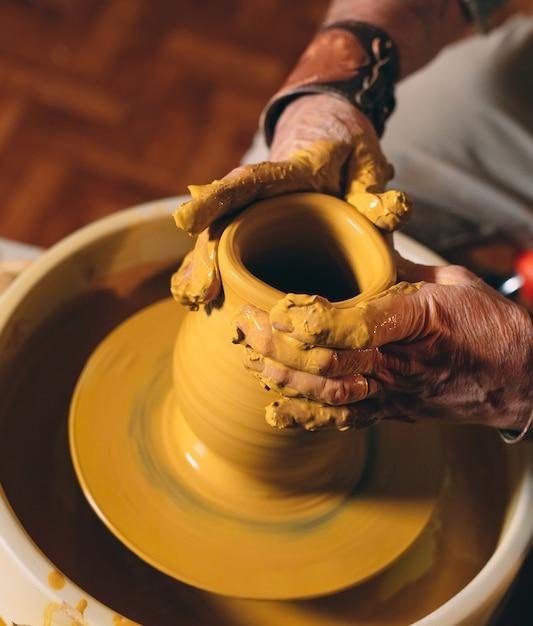 Oficina de cerâmica. um homem sênior faz um vaso de barro. modelagem em argila Foto Premium
