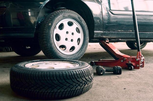 Oficina de pneus e mudança de roda velha no carro Foto Premium
