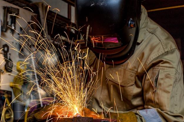 Oficina de soldador treinando um metal de solda com máscara protetora, uniforme e luva na fábrica Foto Premium