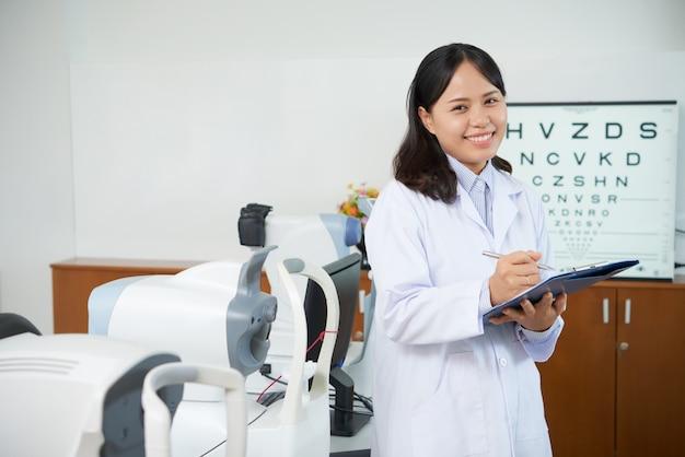 Oftalmologista asiático em pé na sala de exame perto de máquinas de teste de visão Foto gratuita
