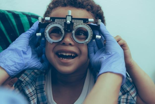 Oftalmologista está examinando os olhos do menino doente Foto Premium