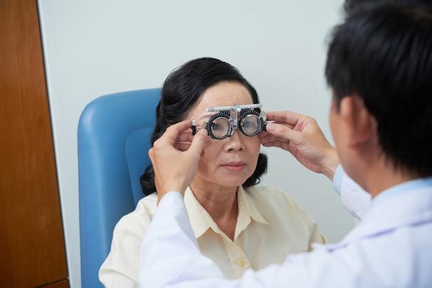 Oftalmologista masculino irreconhecível que encaixa a armação da lente experimental para paciente do sexo feminino sênior Foto gratuita
