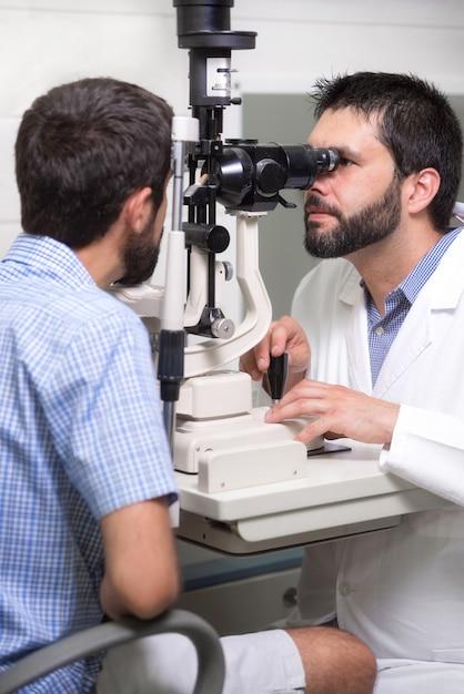 Oftalmologista médico masculino está verificando a visão do olho do jovem bonito na clínica moderna Foto Premium