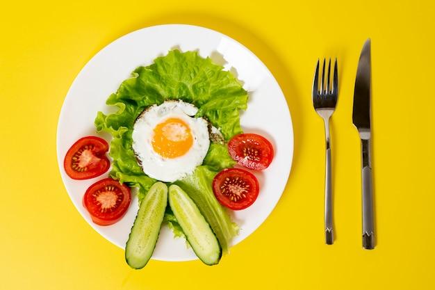 Oito ovos fritos leigos com prato de legumes frescos com talheres no fundo liso Foto gratuita