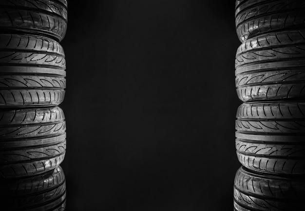 Oito pneus de carro isolados no espaço livre do fundo preto no meio para o texto. Foto Premium