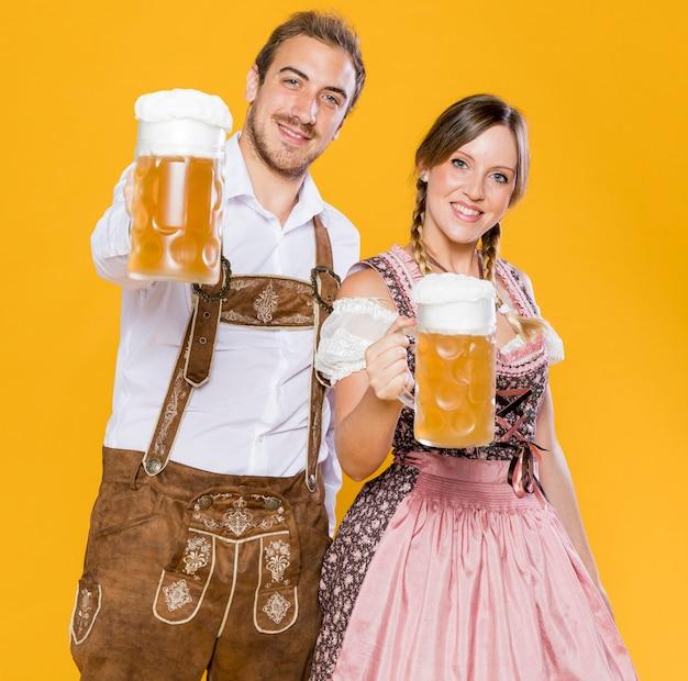 Oktoberfest casal segurando canecas de cerveja Foto Premium