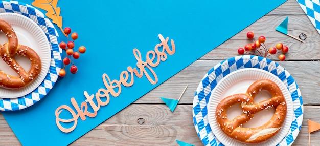 Oktoberfest, plano panorâmico deite na mesa de madeira com papel azul e pretzels em pratos de papel branco azul Foto Premium