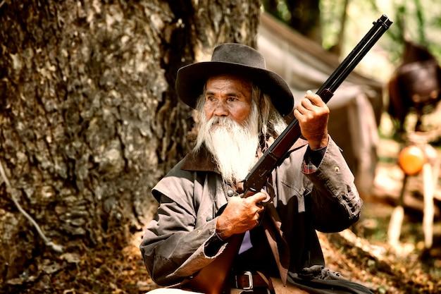 Oldman e arma Foto Premium