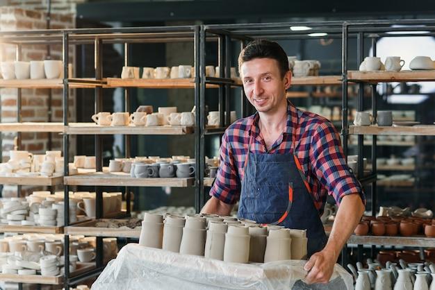 Oleiro masculino caucasiano que guarda a bandeja com os potenciômetros cerâmicos na cerâmica. Foto Premium