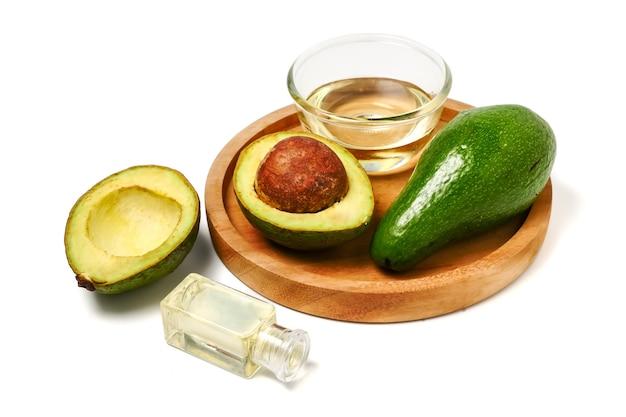 Óleo de abacate e abacate fresco em placa de madeira no fundo branco Foto Premium