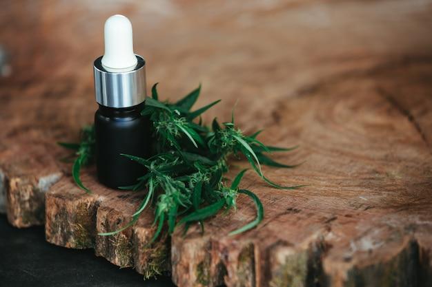 Óleo de cânhamo emparelhado com cânhamo em um piso de madeira marrom. Foto gratuita