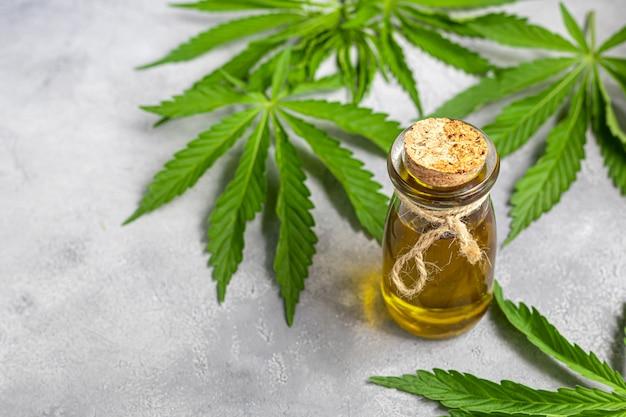 Óleo de cannabis em uma garrafa transparente e folhas de cânhamo em um fundo cinza. Foto Premium