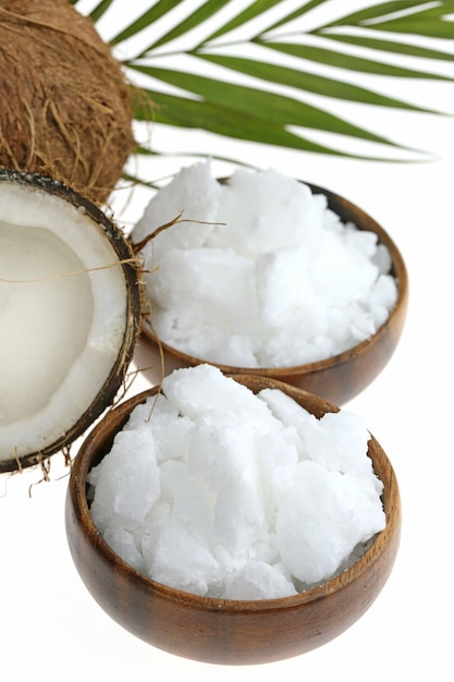 Óleo de coco natural e coco fresco em um corte com folha de palmeira Foto Premium