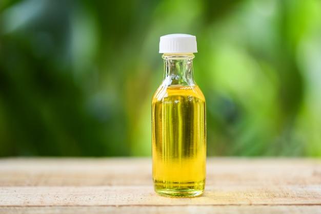 Óleo de gergelim em garrafas de vidro na madeira e natureza verde Foto Premium