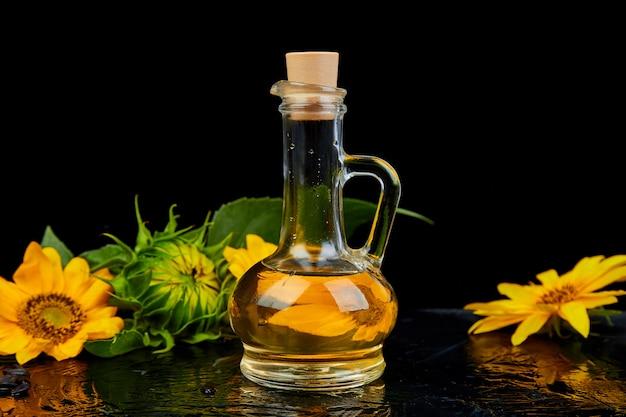 Óleo de girassol em frasco de vidro, sementes e flores Foto Premium