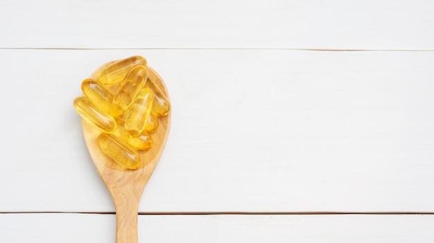 Óleo de peixe em uma colher de pau e mesa de madeira branca. Foto Premium