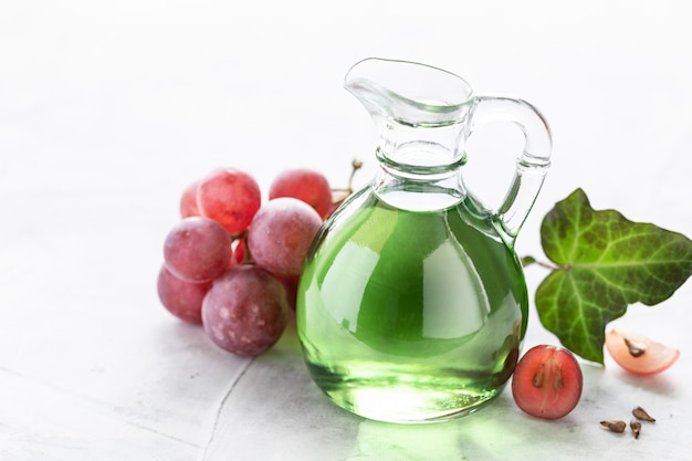 Óleo de semente de uva em uma garrafa de vidro com um cacho de uvas Foto Premium