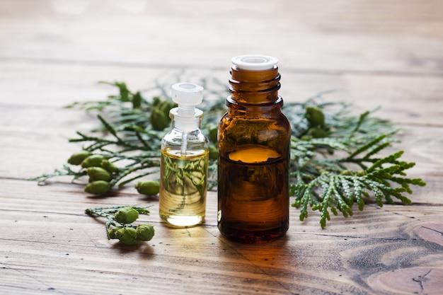 Óleo essencial de aroma de thuja em uma jarra de vidro na superfície de madeira Foto Premium