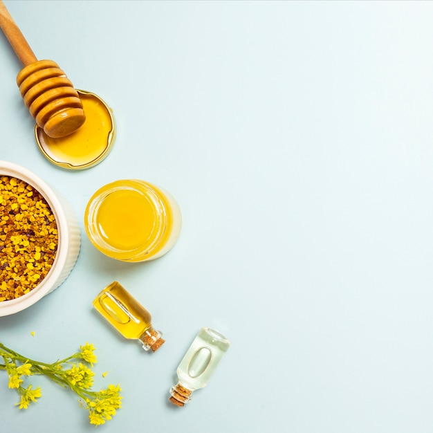Óleo essencial; pólen de abelha e mel com flor fresca amarela sobre fundo azul Foto gratuita